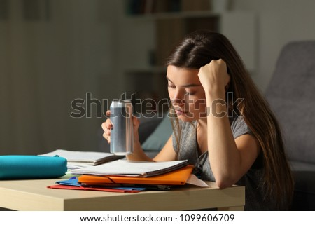Student preparing exam memorizing notes holding and energy drink in the night at home #1099606709