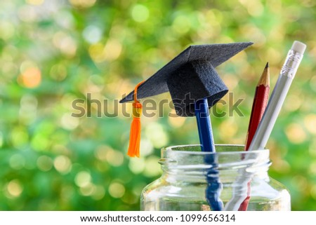Education and knowledge is important for student and most powerful weapon concept : Black graduation cap or hat on pencil in bottle, depicts the power of success in education. Green nature background. #1099656314