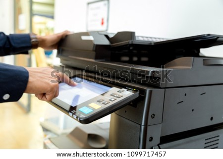Bussiness man Hand press button on panel of printer, printer scanner laser office copy machine supplies start concept. #1099717457