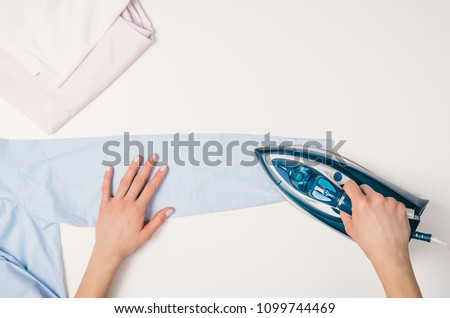 Female hand ironing clothes top view isolated on white background. Young woman with iron ironing shirt seen from above during housework. Blue iron isolated on white table. #1099744469