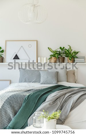 Grey and green blanket on bed against the wall with poster, plants and candles in bedroom interior #1099745756