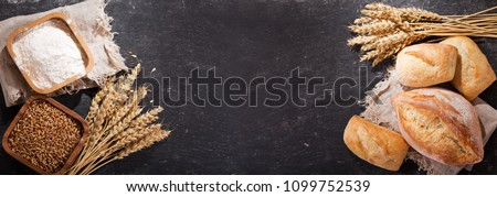 fresh bread with wheat ears and bowl of flour on dark board, top view #1099752539