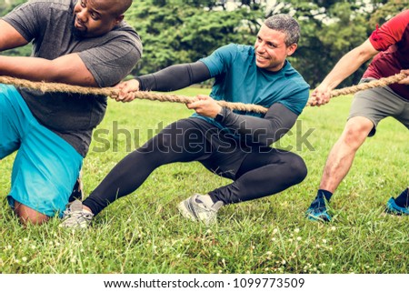 Team competing in tug of war #1099773509