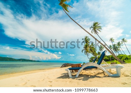Beautiful tropical beach and sea with coconut palm tree and chair in paradise island #1099778663