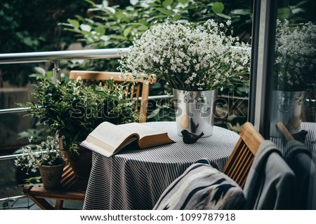 Small table, book and flowers on a beautiful terrace or balcony Royalty-Free Stock Photo #1099787918