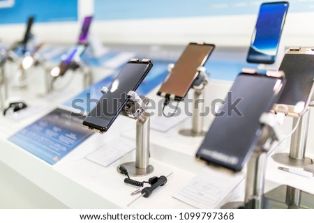 Close up of cell phones or mobile phones on display in a modern, clean and contemporary shop or mall in the UK Royalty-Free Stock Photo #1099797368