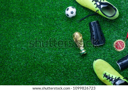 Table top view of soccer or football tournament season background.Flat lay accessories trophy & ball with shoe on the artificial green grass wallpaper.Free space for creative design text and content. #1099826723