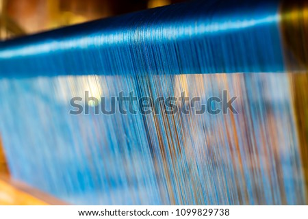 Close Up of Blue Silk on the Weaving machine and Thai traditional Silk. Weaving loom for homemade Silk textile production in Thailand #1099829738