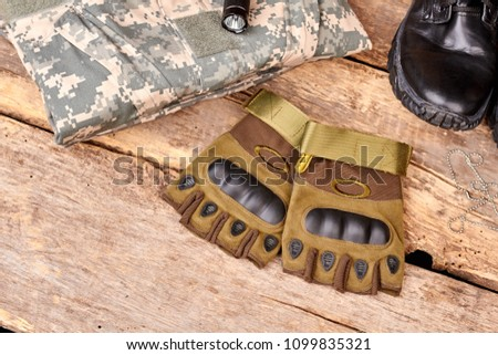 Pair of fingerless gloves and camouflage clothes on wood. Black shoe and torch. Flat lay, top view. #1099835321
