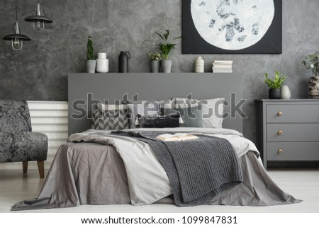 Moon poster on concrete wall above bed with bedhead in grey bedroom interior. Real photo #1099847831