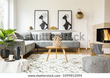 Patterned pouf next to wooden table in african living room interior with posters. Real photo #1099852094
