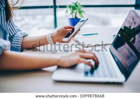 Cropped image of female holding smartphone getting message with confirmation making transaction on laptop computer,woman using mobile phone app for synchronizing data with netbook via bluetooth #1099878668