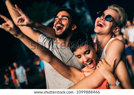 Happy friends having fun at music festival