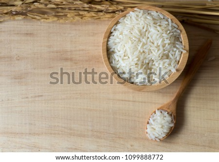 rice in wood bowl and wood spoon on wood background #1099888772