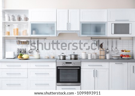 Modern kitchen interior with houseware and new furniture #1099893911