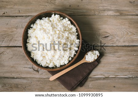 Cottage cheese, curd on rustic wooden table, top view, copy space. Organic bio farm dairy product - homemade cottage cheese. #1099930895