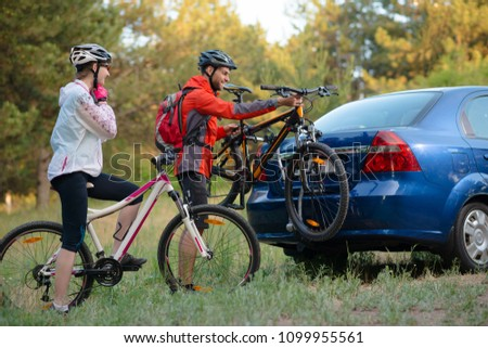 Young Couple Preparing for Riding the Mountain Bikes in the Forest. Unmounting the Bike from Bike Rack on the Car. Adventure and Family Travel Concept. Royalty-Free Stock Photo #1099955561