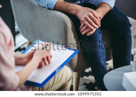 cropped shot of female psychologist listening to male patient and making notes in document on clipboard Royalty-Free Stock Photo #1099975355