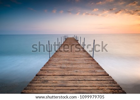 sunset pier wit clouds in the sea of minimalism Royalty-Free Stock Photo #1099979705