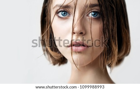 Beautiful young woman with clean perfect skin and wet hair. Portrait of beauty model with natural nude makeup moisturizing her skin. Spa, skincare and wellness. Close up, background, copy space. #1099988993
