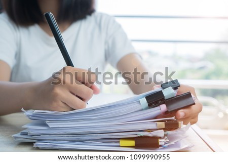 Asian Business woman Manager checking and signing applicant filling documents reports papers company application form or registering claim on desk office. Document Report and business busy Concept