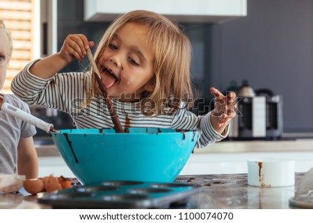 Little girl licking spoon while mixing batter for baking in kitchen  and her brother standing by. Cute little children making batter for baking. Royalty-Free Stock Photo #1100074070