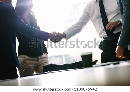 Partners concluding deal and shaking hands in the presence of team members. Businessmen shaking hands in board room and finishing up a meeting. #1100075942