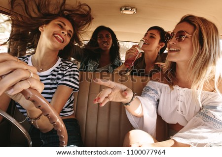 Group of happy young women laughing and enjoying in car during a road trip to vacation. Girls having fun on road trip. #1100077964