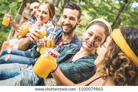 Happy friends drinking healthy orange fruit juice at countryside picnic - Young people millennials having fun together outdoors on afternoon snack at garden -  Friendship concept in nature environment