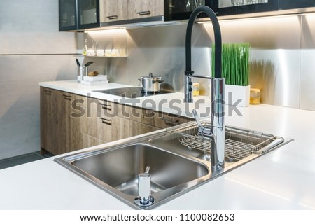 Stainless kitchen sink and Tap water in the kitchen. The interior of the kitchen room of the apartment. Built-In Appliances. Kitchen Appliance. Domestic Appliances #1100082653