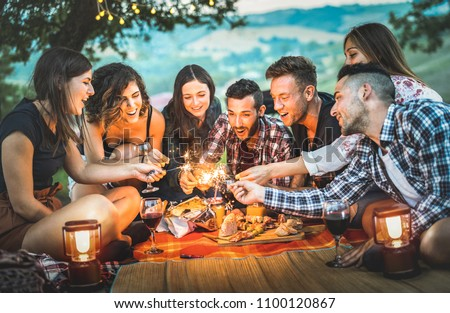 Happy friends having fun with fire sparkles - Young people millennials camping at picnic after sunset - Young people enjoying wine at summer barbecue party - Youth friendship concept on night mood #1100120867