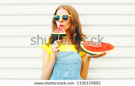 Pretty girl eating a slice of watermelon in the form of ice cream over a white background #1100159882