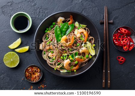 Stir fry noodles with vegetables and shrimps in black bowl. Slate background. Top view. #1100196590