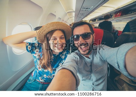 Young handsome couple taking a selfie on the airplane during flight around the world. They are a man and a woman, smiling and looking at camera. Travel, happiness and lifestyle concepts. #1100286716