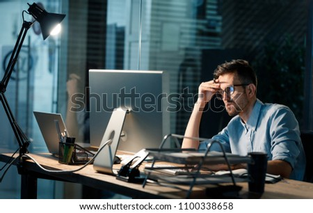 Casual tired office worker sitting at desk using computer and doing overtime project in lamplight.  Royalty-Free Stock Photo #1100338658