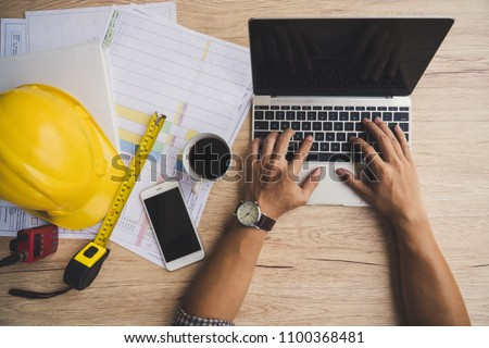 architect man working with laptop and blueprints : sketching a construction project ,engineer inspection in workplace for architectural plan, selective focus, Business concept vintage color.