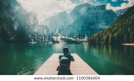 Travel hiker taking photo of Lake Braies (Lago di Braies) in Dolomites Mountains, Italy. Hiking travel and adventure. Royalty-Free Stock Photo #1100386004