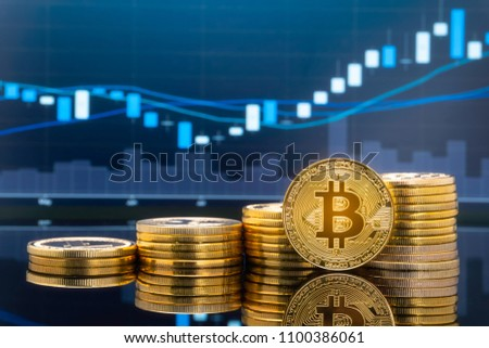 Bitcoin and cryptocurrency investing concept - Physical metal Bitcoin coins with global trading exchange market price chart in the background. #1100386061