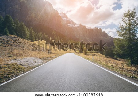 Beautiful mountain road with trees, forest and mountains in the backgrounds. Taken at state highway road in Passo Gardena, Sella mountain group of Dolomites mountain in Italy. #1100387618