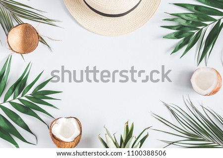 Summer composition. Tropical palm leaves, hat, coconut on pastel blue background. Summer concept. Flat lay, top view, copy space #1100388506