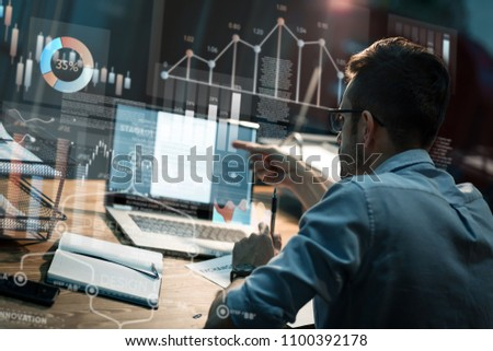 Man in eyeglasses watching monitor of computer sitting alone late at night in office having overhours. #1100392178
