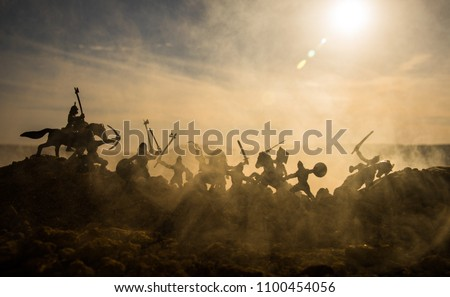 Medieval battle scene with cavalry and infantry. Silhouettes of figures as separate objects, fight between warriors on sunset foggy background. Selective focus #1100454056