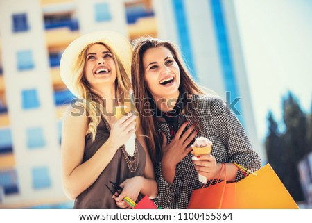 Happy young women with shopping bags and ice cream having fun on city street #1100455364