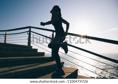 Sporty fitness female runner running up on seaside stairs #1100474726