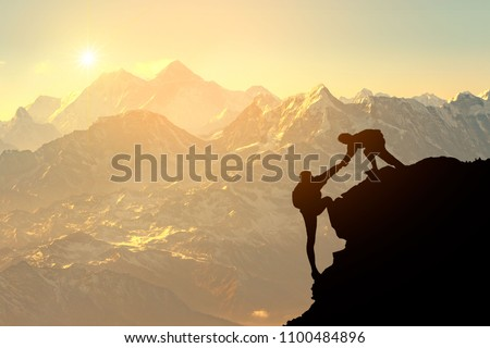 Asia couple hiking help each other silhouette in mountains with sunlight. Royalty-Free Stock Photo #1100484896