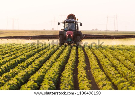Tractor spraying pesticides on soybean field with sprayer at spring #1100498150