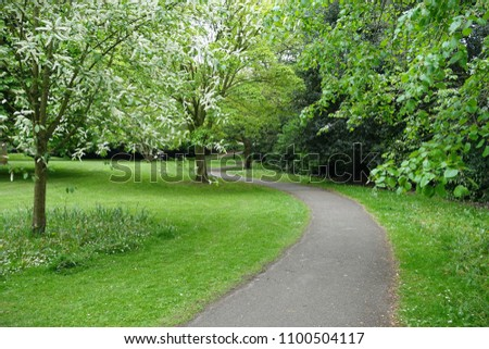 Scenic View of Path through a Beautiful Green Leafy Park Garden #1100504117
