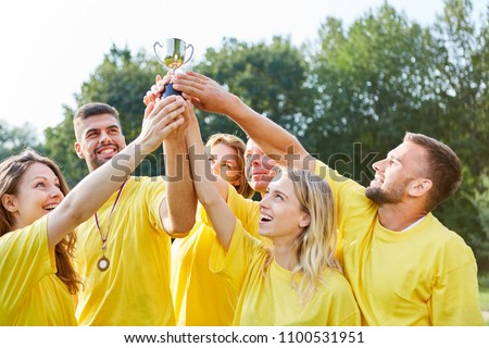 Happy Winners Team proudly holds the trophy high in the Teambuilding Event #1100531951