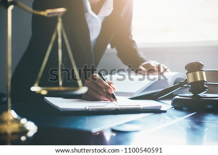 Justice and Law concept. Legal counsel presents to the client a signed contract with gavel and legal law or legal having team meeting at law firm in background #1100540591