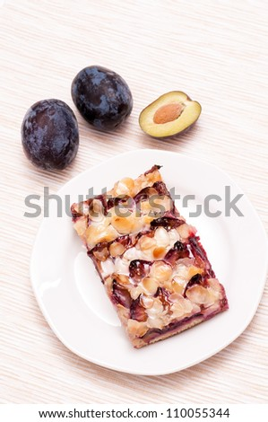 Plum cake on a plate with three plums #110055344
